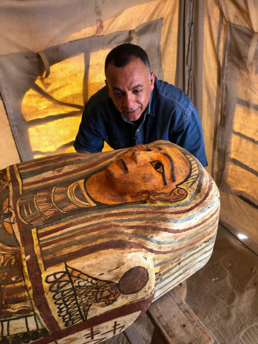 A handout picture released by the Egyptian Ministry of Antiquities on September 20, 2020, shows Secretary General of the Supreme Council of Antiquities Mostafa Waziri (C) inspecting one of fourteen 2500 year-old coffins discovered in a burial shaft at the desert necropolis of Saqqara south of the capital. - Egypt's antiquities ministry announced the discovery of 14 new coffins in the Saqqara area buried deep in a well for around 2500 years. (Photo by - / Egyptian Ministry of Antiquities / AFP)